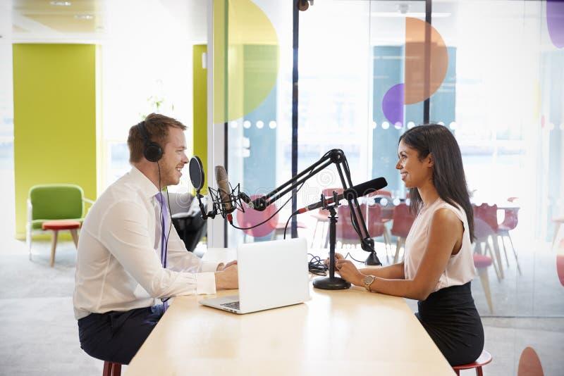 Ung man som intervjuar en kvinna för en podcast royaltyfria foton