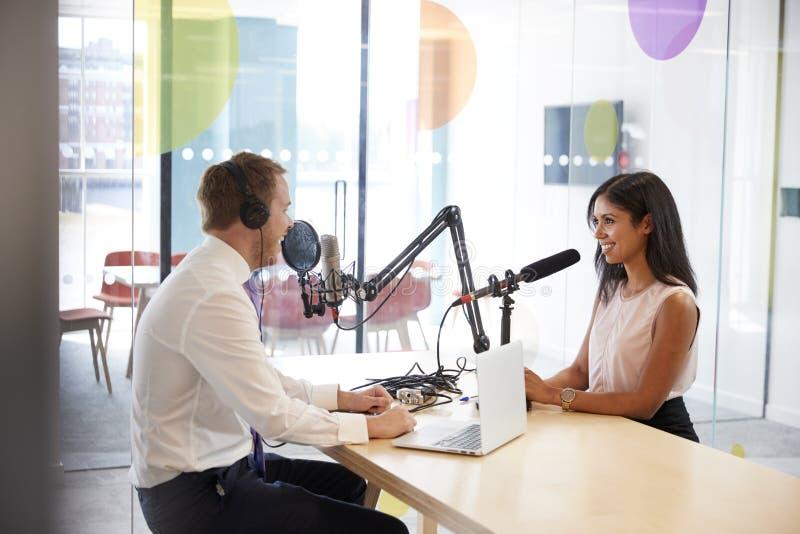 Ung man som intervjuar en kvinna i en radiostudio royaltyfri bild