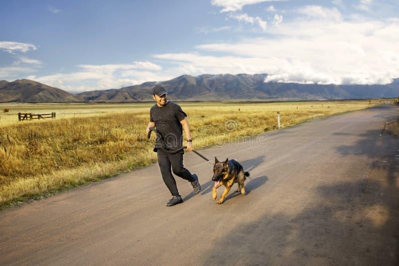 Ung man som joggar med hans hund på vägen arkivbilder