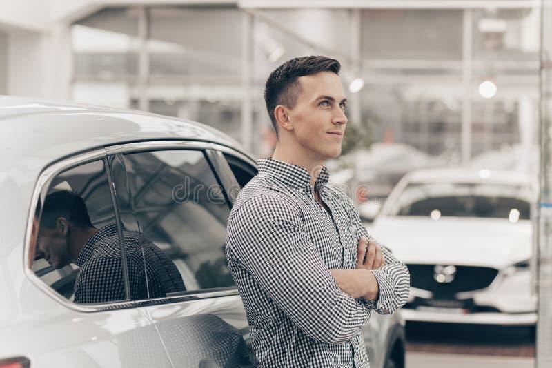 Ung man som köper den nya bilen på återförsäljaren fotografering för bildbyråer