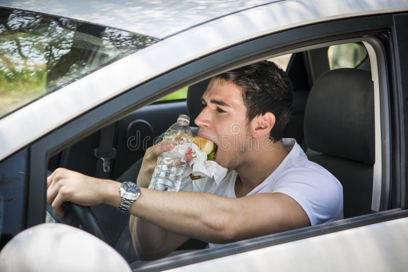Ung man som kör hans bil, medan äta mat royaltyfri bild