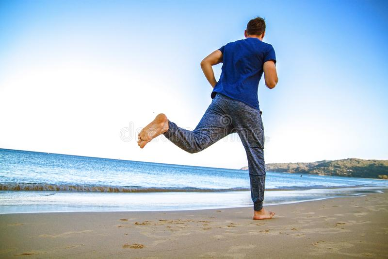 Ung man som kör på stranden i sportkläder royaltyfri foto