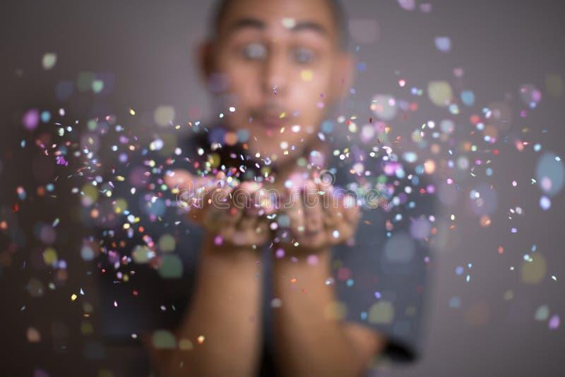 Ung man som kastar konfettier arkivfoto