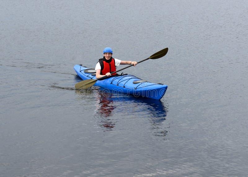 Ung man som kayaking på den stora sjön arkivfoto