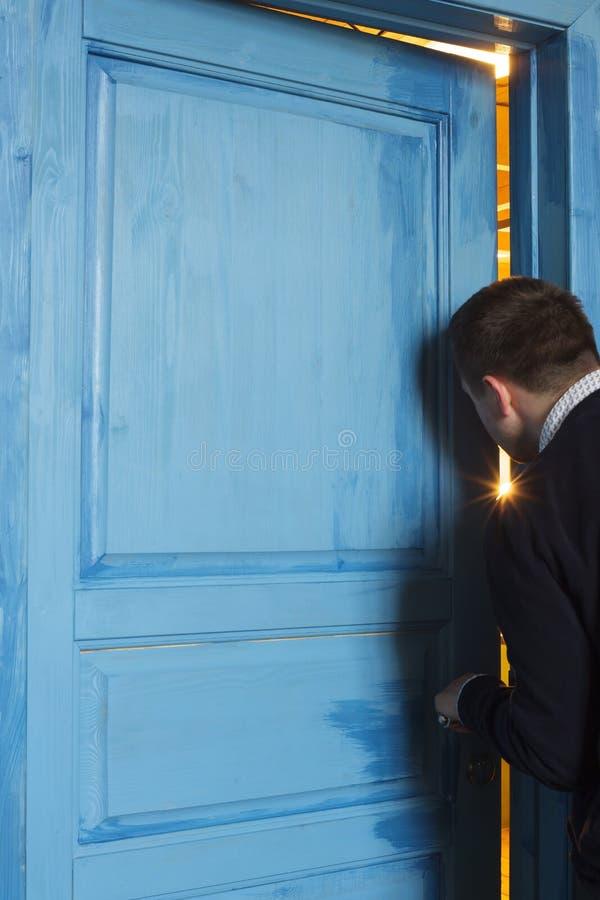 Ung man som kikar i dörrspringan arkivbild