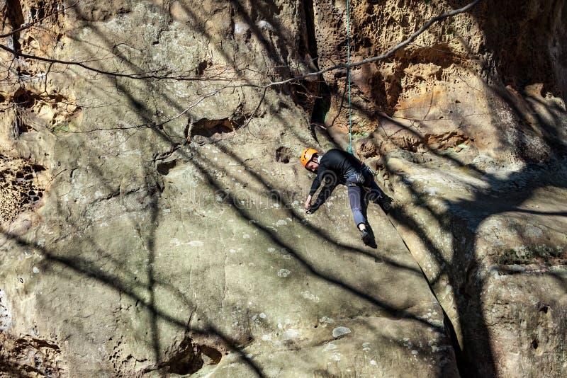 Ung man som klättrar sandstenklippan i skogen på den soliga dagen royaltyfria foton