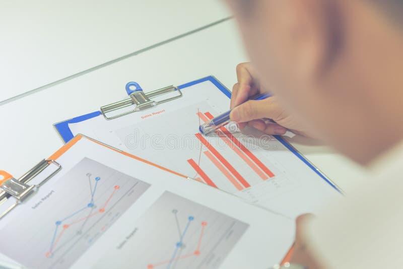 Ung man som kontrollerar data på finansiell rapport arkivfoto