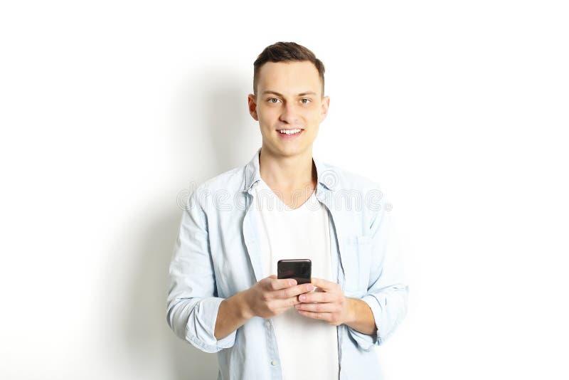 Ung man som kontrollerar mobiltelefonen som läser ett meddelande Teknologi- & förhållandebegrepp Moderna romansproblem Manlig & k royaltyfria foton