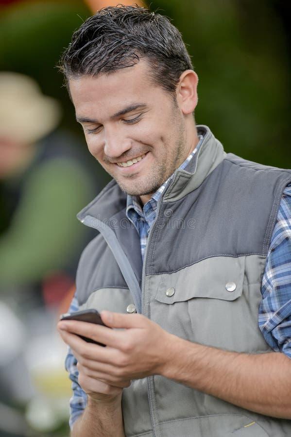 Ung man som kontrollerar telefonen arkivfoto
