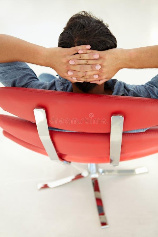 Ung man som kopplar av i röd stol arkivfoton