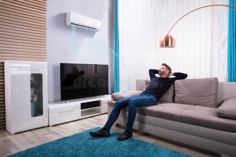 Ung man som kopplar av på soffan fotografering för bildbyråer