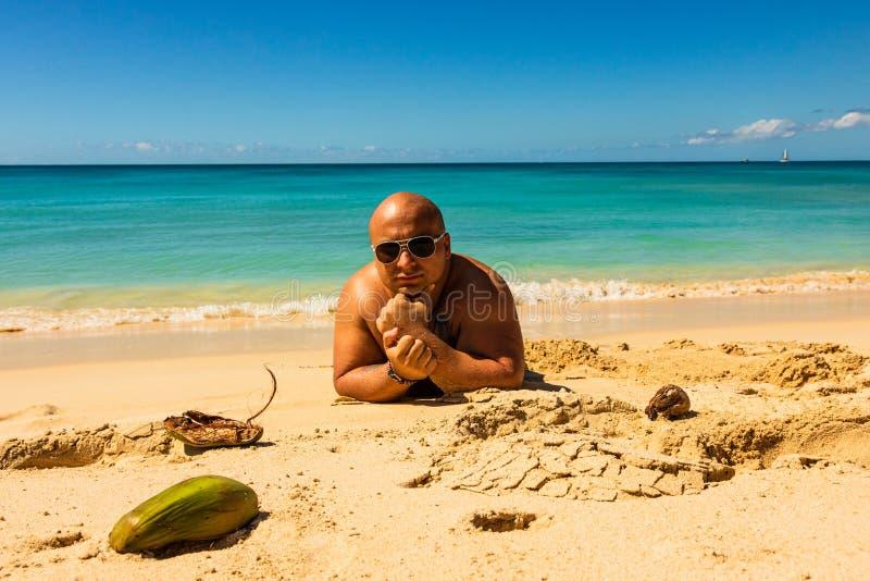 Ung man som kopplar av sanden av den Barbados stranden Idyllisk eftermiddag på stranden i karibiska öar royaltyfri bild