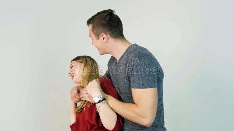 Ung man som kramar flickvännen Barnet kopplar ihop omfamningar efter ett långt avskiljande, på en vit bakgrund royaltyfri bild