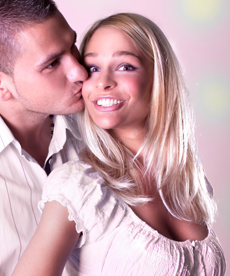 Ung man som kysser en lycklig kvinna royaltyfri foto