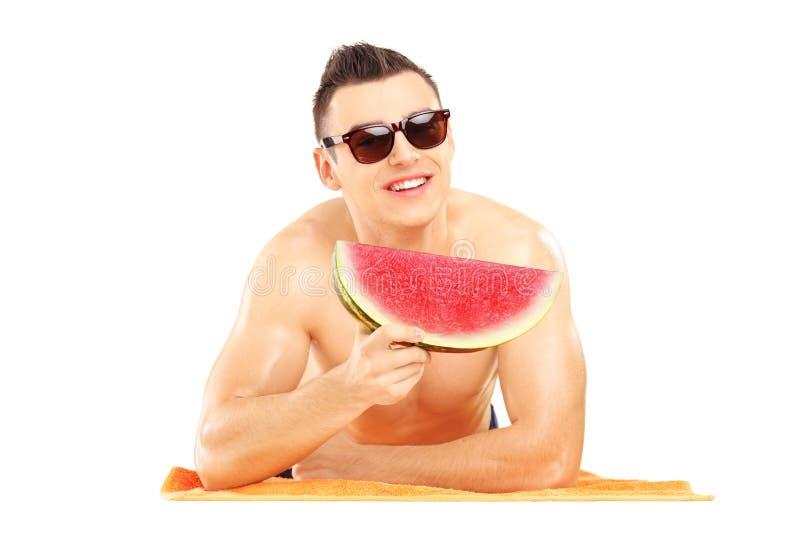 Ung man som lägger på en strandhandduk och äter en skiva av watermel arkivbild