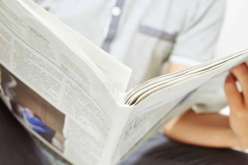 Ung man som läser tidningen royaltyfri foto