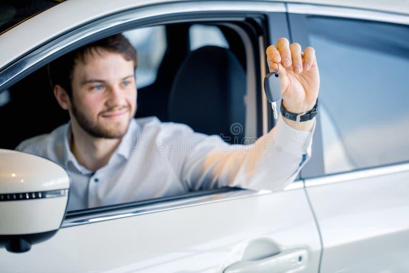 Ung man som ler och hurrar i hans bil royaltyfri bild