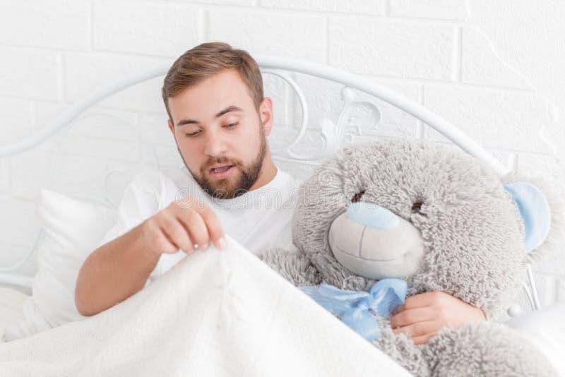 Ung man som ligger i säng med en nallebjörn och ser under filten royaltyfri foto