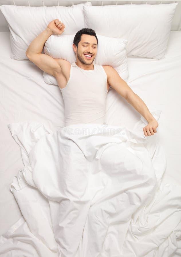 Ung man som ligger, i säng och sträckning royaltyfria foton