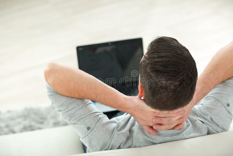 Ung man som ligger på den hållande ögonen på videoen för soffa på bärbara datorn arkivfoto