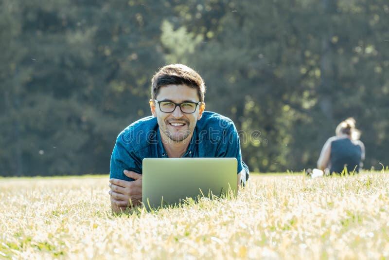 Ung man som ligger på gräs och använder bärbara datorn arkivfoton