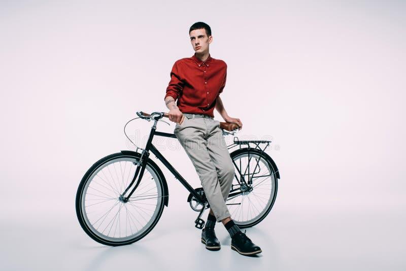 Ung man som lutar på hans cykel arkivfoton