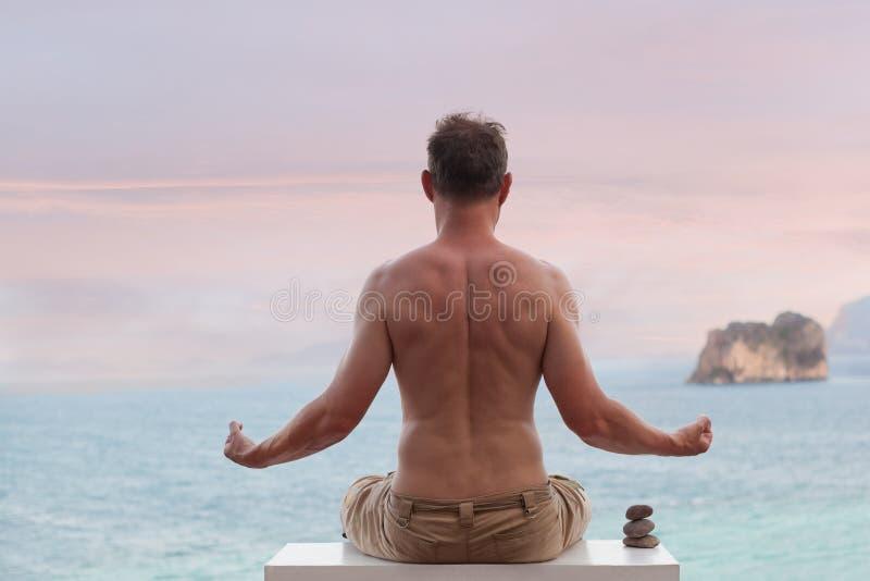 Ung man som mediterar eller gör yogaövningar arkivbild
