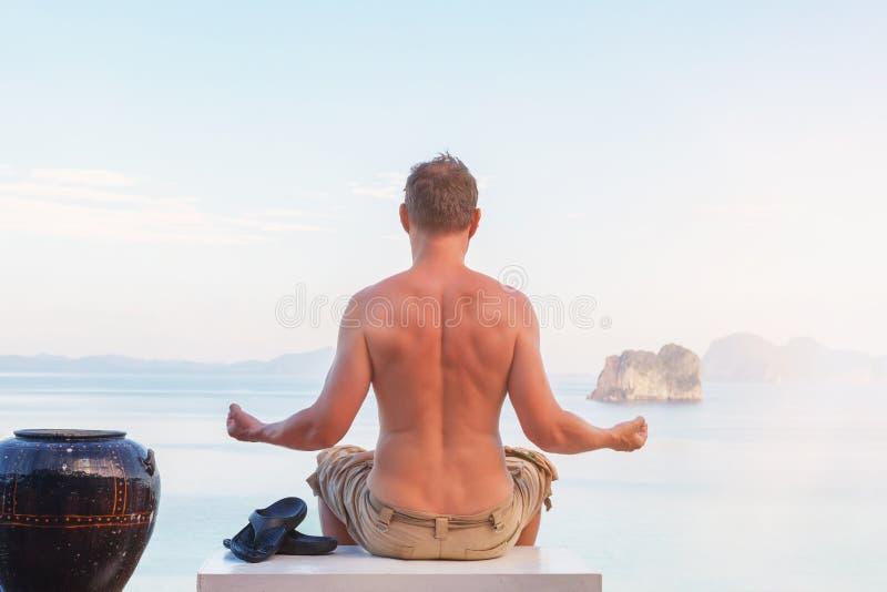Ung man som mediterar förbise havet royaltyfria bilder