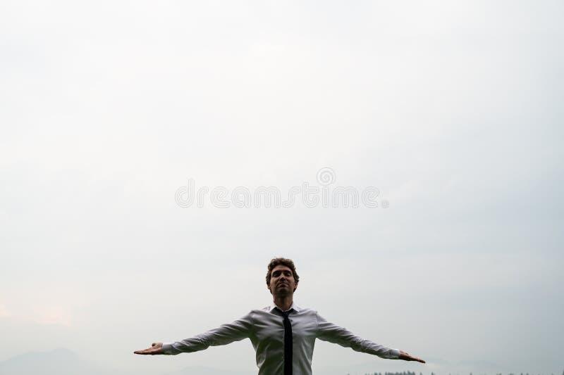 Ung man som mediterar under molnig himmel arkivfoton