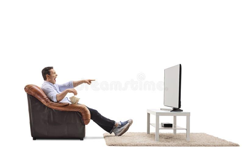 Ung man som placeras i en hållande ögonen på television och skratta för fåtölj royaltyfria bilder