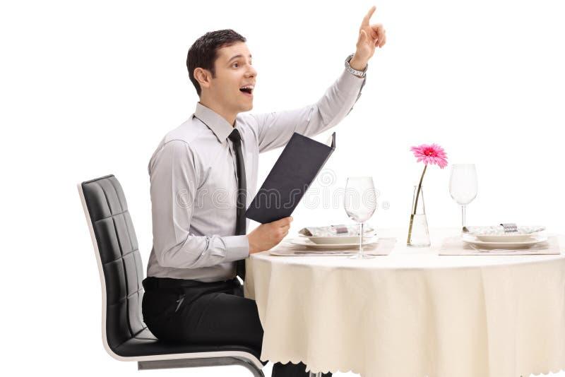 Ung man som placeras på en restaurangtabell som kallar uppassaren fotografering för bildbyråer