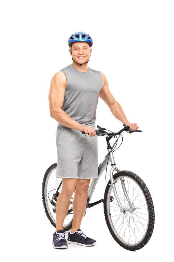 Ung man som poserar bredvid hans cykel och le royaltyfria foton