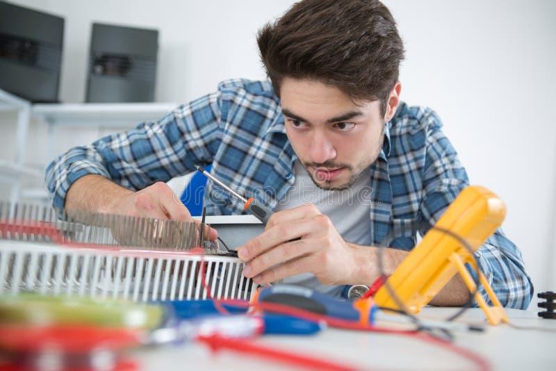 Ung man som reparerar elementet arkivfoto