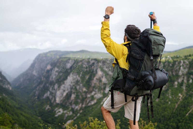 Ung man som reser med ryggsäcken som fotvandrar i berg royaltyfria bilder