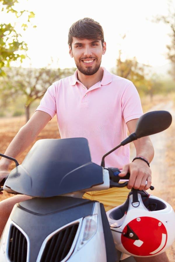 Ung man som rider den motoriska sparkcykeln längs landsvägen arkivbild