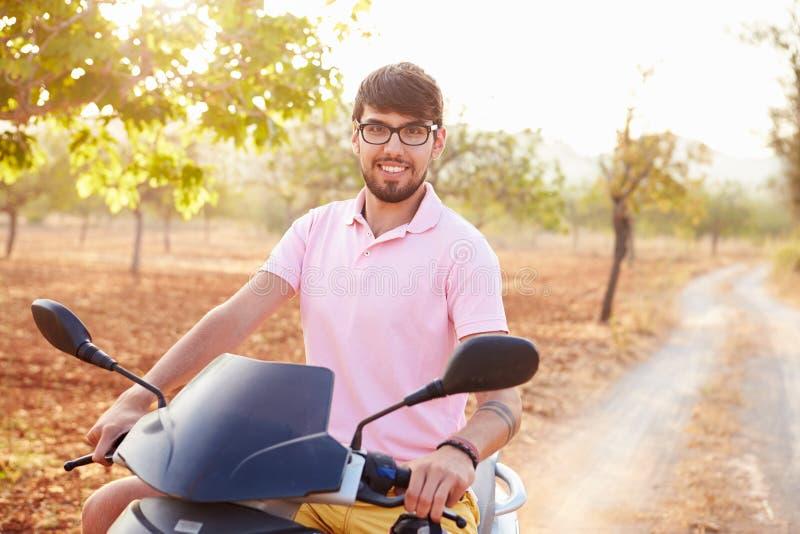 Ung man som rider den motoriska sparkcykeln längs landsvägen royaltyfri fotografi