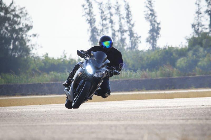 Ung man som rider den stora cykelmotorcykeln mot skarp kurva av den höga vägvägen för asfalt med lantligt sjöplatsbruk för manlig arkivfoto