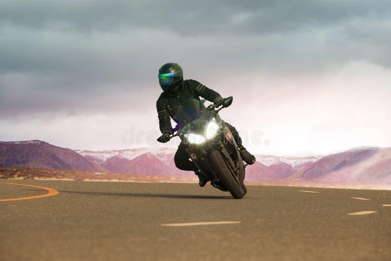Ung man som rider den stora motorcykeln på asfalthuvudvägen, bruk för peop arkivbilder