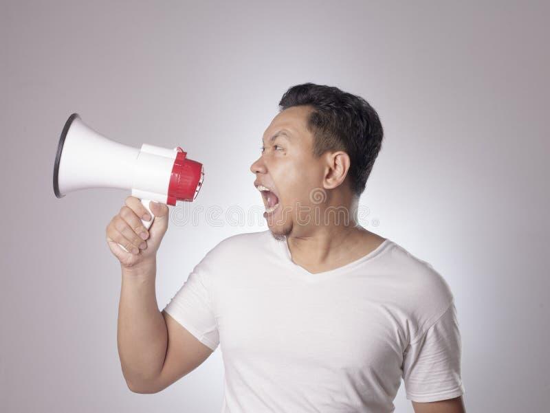Ung man som ropar med megafonen, ilsket uttryck arkivbild