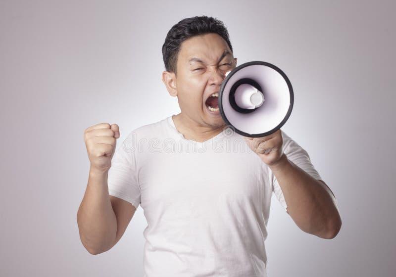 Ung man som ropar med megafonen, ilsket uttryck arkivfoton
