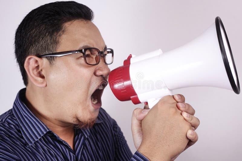 Ung man som ropar med megafonen, ilsket uttryck royaltyfri fotografi