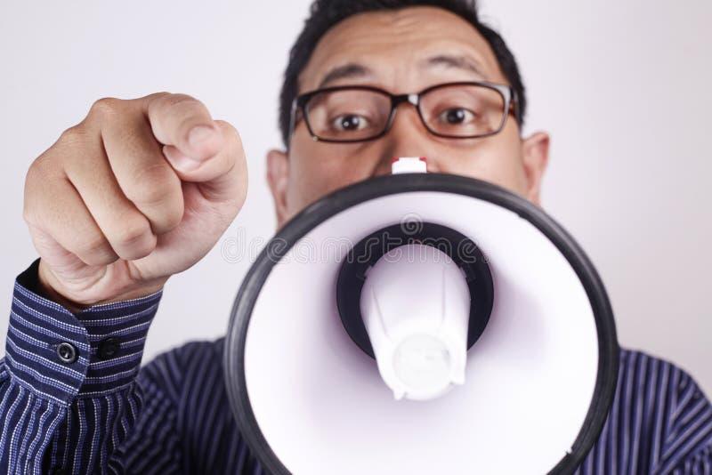 Ung man som ropar med megafonen, ilsket uttryck royaltyfri foto