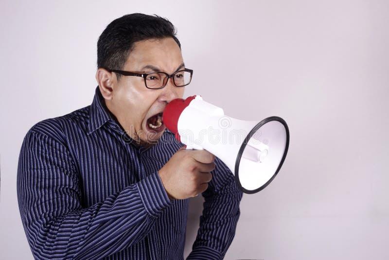 Ung man som ropar med megafonen, ilsket uttryck arkivfoto