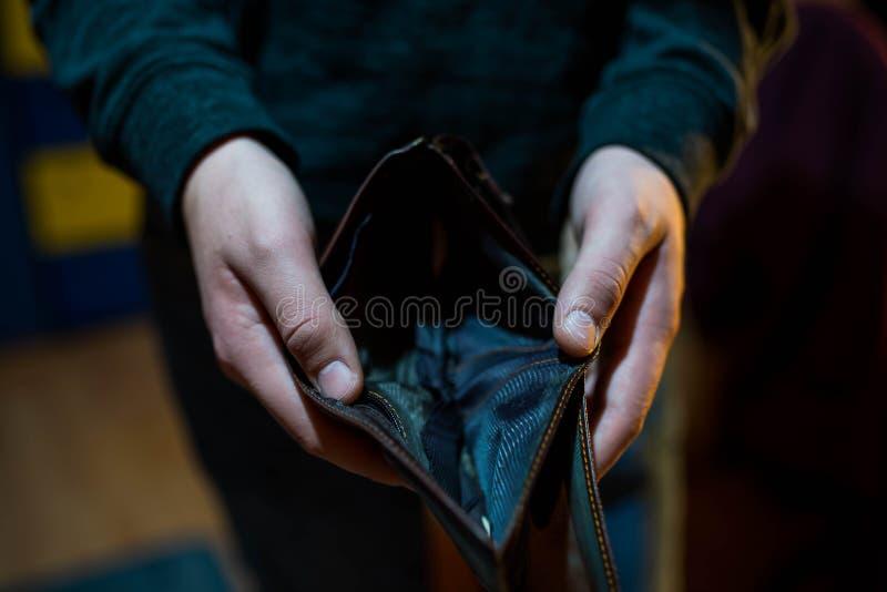 Ung man som rymmer den tomma plånboken, fokus på handen, royaltyfri fotografi