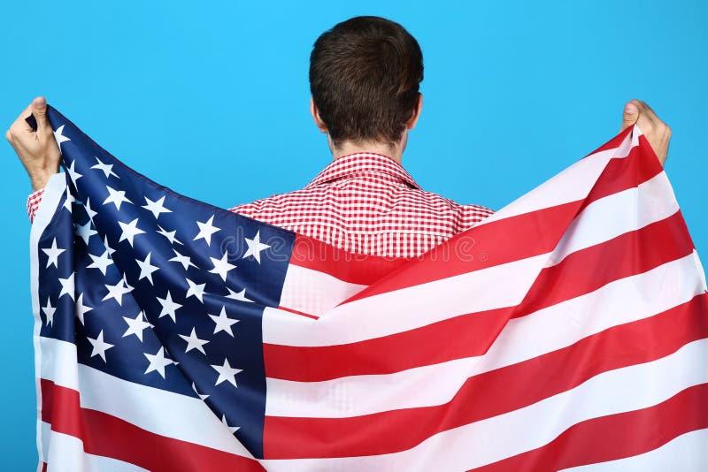 Ung man som rymmer en amerikanska flaggan royaltyfria bilder