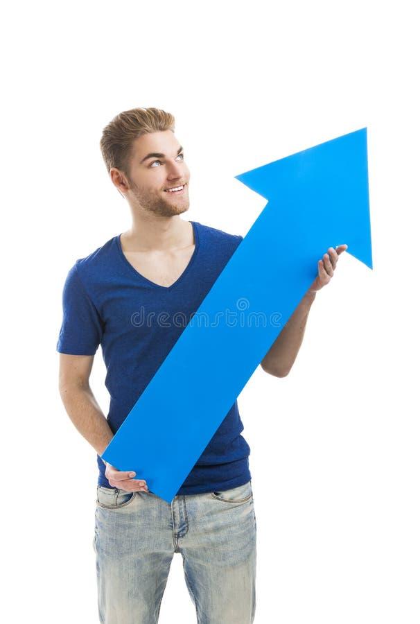 Ung man som rymmer en blå pil fotografering för bildbyråer