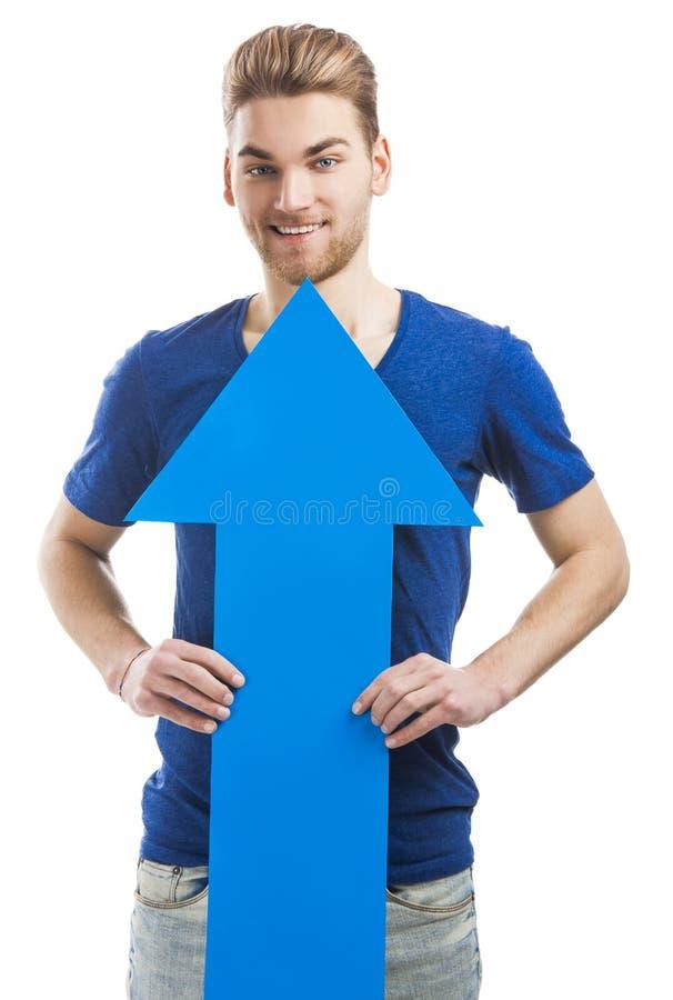 Ung man som rymmer en blå pil royaltyfria foton