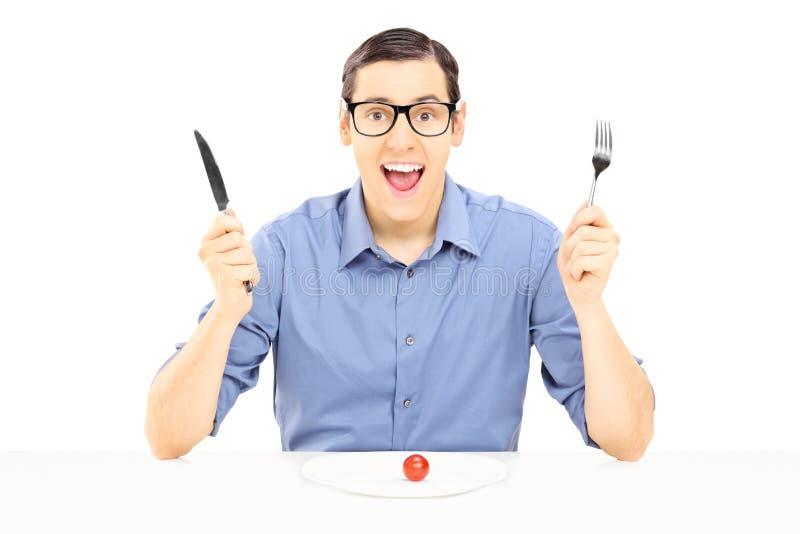 Ung man som rymmer en gaffel och en sked som äter den körsbärsröda tomaten arkivfoton