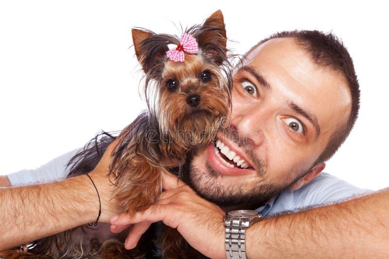 Ung man som rymmer en gullig yorkievalphund fotografering för bildbyråer