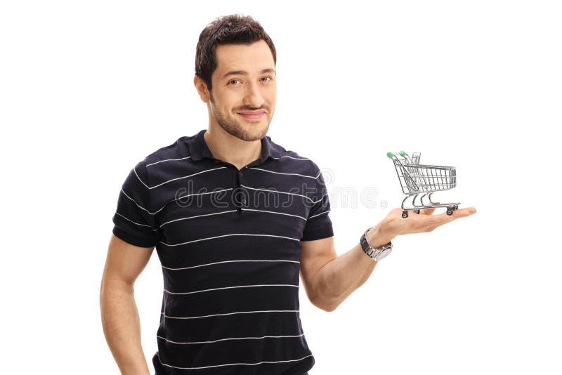 Ung man som rymmer en liten tom shoppingvagn arkivbilder